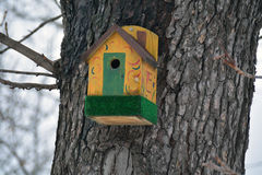 Ornate yellow birdhouse on the trunk in the park Royalty Free Stock Photography