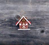 Ornement décoratif de Noël - durcissez la maison sur le fond en bois Photographie stock