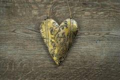 Ornement d'or rustique de coeur sur le fond en bois de vintage Images libres de droits