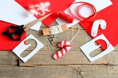 Ornement de canne de sucrerie d'arbre de Noël de feutre, ciseaux, calibre de papier, fil, aiguille, morceaux rouges et blancs et  Photos stock