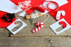 Ornement de canne de sucrerie de Noël de feutre, ciseaux, calibre de papier, fil, aiguille, morceaux rouges et blancs de feutre e Photographie stock libre de droits
