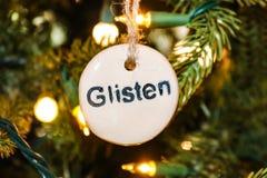 Ornement embouti de Noël de scintillement sur l'arbre avec des ficelles des lumières Image stock