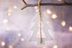 Ornement en bois fait main d'arbre de Noël blanc accrochant sur la branche Lumières éclatantes de guirlande Seul arbre congelé Ca Images libres de droits