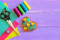 Ornement lumineux de coeur pour le jour de valentines L'ornement de coeur de feutre, fil, ciseaux, feutre coloré couvre, dé Image libre de droits