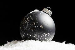 Ornement noir et argenté éclatant se reposant dans la neige, brillant dedans Images stock