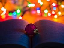 Ornement rouge de Noël de scintillement sur un livre ouvert avec des lumières de Noël à l'arrière-plan photographie stock
