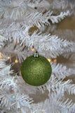 Ornement vert de scintillement de Noël sur l'arbre blanc Photo libre de droits