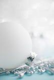 Ornements blancs de Noël sur le fond de bokeh de scintillement Carte de Joyeux Noël Photographie stock libre de droits