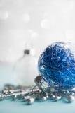 Ornements blancs et bleus de Noël sur le fond de bokeh de scintillement Carte de Joyeux Noël Photographie stock libre de droits