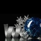 Ornements bleus et argentés de Noël sur le fond noir photo libre de droits