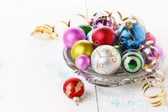 Ornements colorés de Noël au-dessus du fond blanc Images stock