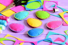 Ornements d'oeufs de pâques de feutre, feuilles de feutre et chutes colorés, ciseaux, fil, dé sur une table Photographie stock libre de droits