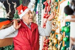 Ornements de achat de Noël d'homme au magasin Photos stock