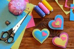 Ornements de jour de valentines Ornements de coeur de feutre, ciseaux, fil, pelote à épingles, dé, feuilles de feutre et morceaux Photos stock