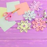 Ornements de papier colorés de flocons de neige, feuilles de papier coloré et chute, ciseaux sur le fond en bois lilas Images libres de droits