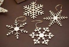 Ornements en bois de flocons de neige de coupe de laser Flocons de neige en bois sur le fond de Brown Noël Holliday Concept Image libre de droits