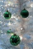 Ornements et lumières verts colorés de clignotement sur l'arbre de Noël blanc Photographie stock libre de droits