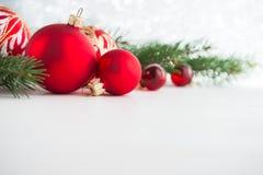 Ornements rouges de Noël sur le fond en bois Carte de Joyeux Noël images stock