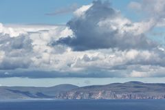 Orney cliffs with dramatic sky seen from John o`Groats over Atlantic ocean.  stock images