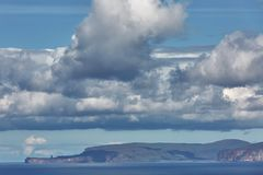 Orney cliffs with dramatic sky seen from John o`Groats over Atlantic ocean.  royalty free stock photography