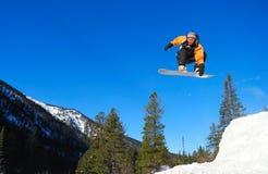 Ornge die snowboarder hoog springt Royalty-vrije Stock Foto