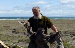 Ornitólogo con un pájaro muerto en el golfo de Inutil Fotografía de archivo libre de regalías