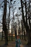 Ornitólogo femenino joven observando grajos el jerarquizar arriba para arriba en árboles en la primavera - Bauska, Letonia, 2019 imágenes de archivo libres de regalías