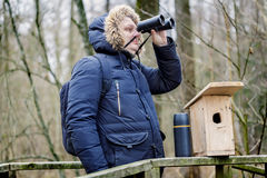 Ornithologist with binoculars and bird cage in the park on the bridge Royalty Free Stock Images