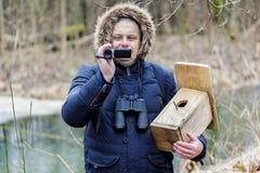 Ornitolog med camcorder- och fågelburen nära floden arkivfoton