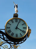 Ornnate gold street clock. With roman numerals and statue Stock Images