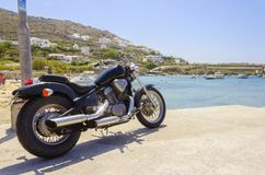 Ornos beach, Mykonos, Greece. An old vintage motorbike parked at Ornos beach in Mykonos, Greece. A concept of freedom, summer and holiday vacations on the Royalty Free Stock Photo