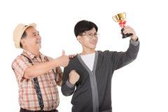 Oro asiatico della tazza della tenuta del giovane Fotografie Stock Libere da Diritti
