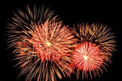 Oro asombroso y fuegos artificiales rojos en fondo oscuro Fotografía de archivo libre de regalías