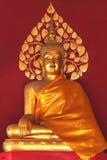 Oro buddha con el fondo rojo de la pared fotografía de archivo libre de regalías