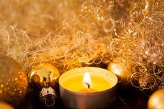 Oro caliente y fondo rojo de la luz de una vela de la Navidad Foto de archivo