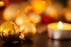Oro caliente y fondo rojo de la luz de una vela de la Navidad Fotos de archivo