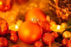 Oro caliente y fondo rojo de la luz de una vela de la Navidad Imagen de archivo