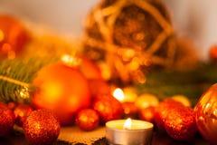 Oro caliente y fondo rojo de la luz de una vela de la Navidad Foto de archivo libre de regalías
