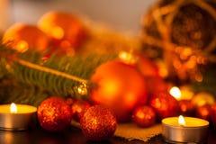 Oro caliente y fondo rojo de la luz de una vela de la Navidad Fotografía de archivo libre de regalías