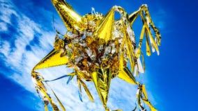 Oro colorido grande y piñata mexicano de plata contra un cielo azul, con las nubes blancas imágenes de archivo libres de regalías