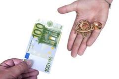 Oro contra el dinero del efectivo Foto de archivo