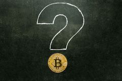 Oro de Bitcoin en el tablero con un signo de interrogación Imagenes de archivo
