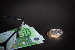 Oro de Bitcoin y moneda de plata en un primer negro del fondo foto de archivo libre de regalías