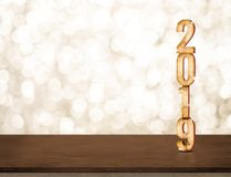 Oro 2019 de la Feliz Año Nuevo brillante con la estrella chispeante en la frente oscura Foto de archivo