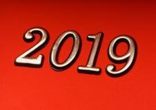 Oro 2019 de la plantilla del diseño de la tarjeta de felicitación en letras rojas Foto de archivo libre de regalías