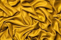 Oro del tessuto dei drappi Priorità bassa ondulata Immagine Stock Libera da Diritti