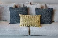 Oro e cuscini neri di colore sul sofà grigio Immagini Stock