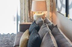 Oro e cuscini neri di colore sul sofà grigio Fotografia Stock Libera da Diritti