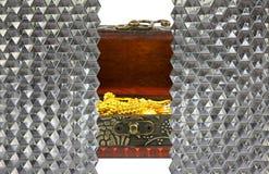 oro en cofre del tesoro antiguo detrás del vidrio cristalino del hexágono de la pared Imágenes de archivo libres de regalías