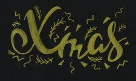 Oro moderno elegante manuscrito de la inscripción de los cepillos de Navidad en letras de oro del cepillo del fondo negro Fotografía de archivo libre de regalías